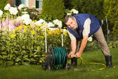 Man crimping hose in the garden — Stock Photo