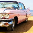 Classic pink car at beach — Stockfoto