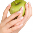 Green apple in woman's hands — Stock Photo