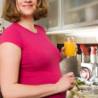 Stock Photo: Woman in kitchen making a salad