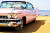 Classic pink car at beach — Stock fotografie
