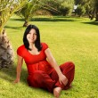 Pregnant woman sitting on the grass — Stock Photo