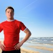 Young man standing at beach — Stock Photo
