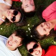 Stock Photo: Group of friends lying on grass