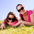 Two girls relaxing in a park - Stock Photo