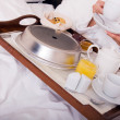 Woman with breakfast in bed — Stock Photo
