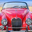 Old classic red car at the beach - Stockfoto