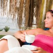 Woman having a cup of coffee in bungalow — Stock Photo