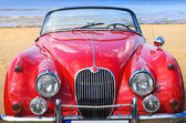 Old classic red car at the beach — Stock Photo