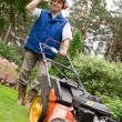 Stok fotoğraf: Senior man mowing the lawn.