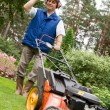 Stock Photo: Senior mmowing lawn.