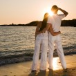 Royalty-Free Stock Photo: Couple hugging, enjoying summer sunset.