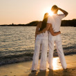 Stock Photo: Couple hugging, enjoying summer sunset.