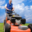 Stockfoto: Senior man mowing the lawn.