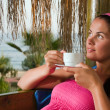 Stock Photo: Womhaving cup of coffee in bungalow