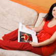 Pregnant woman sitting on the couch - Stock Photo