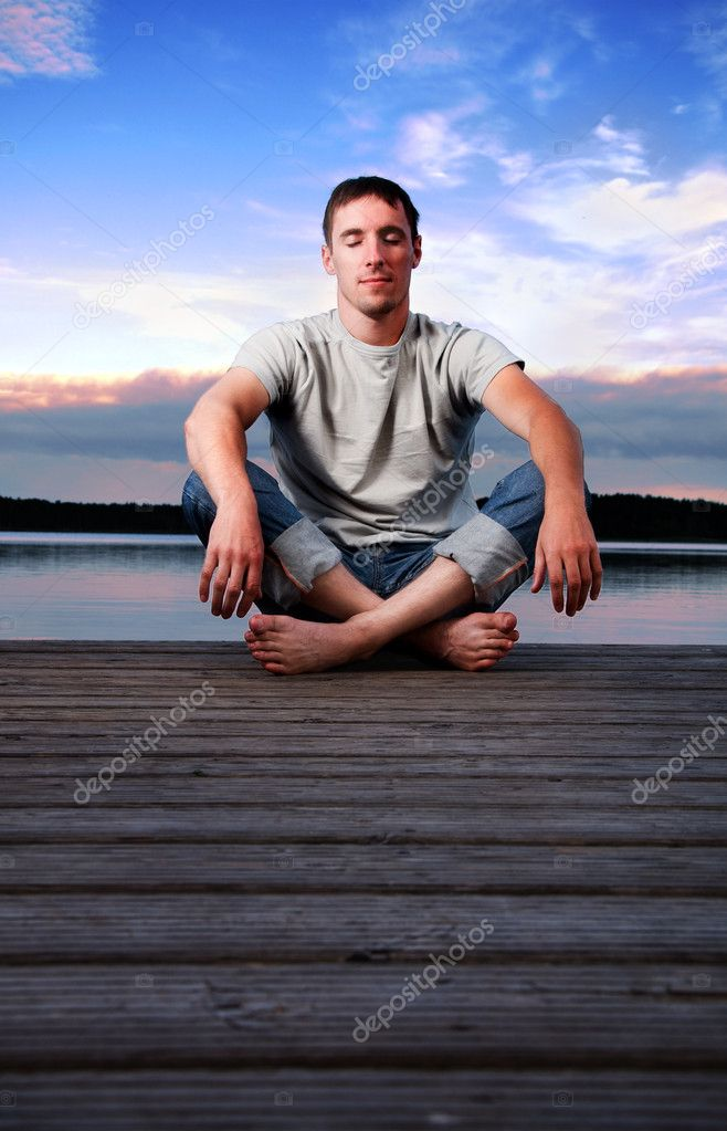 A young man sitting alone near the water in the evening  Lizenzfreies Foto #1990579