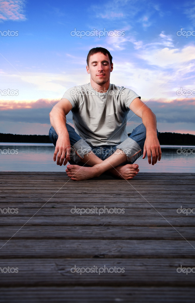 A young man sitting alone near the water in the evening  Zdjcie stockowe #1990579