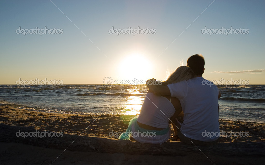 Couple sitting near the sea on sunset   Stock Photo #1991441