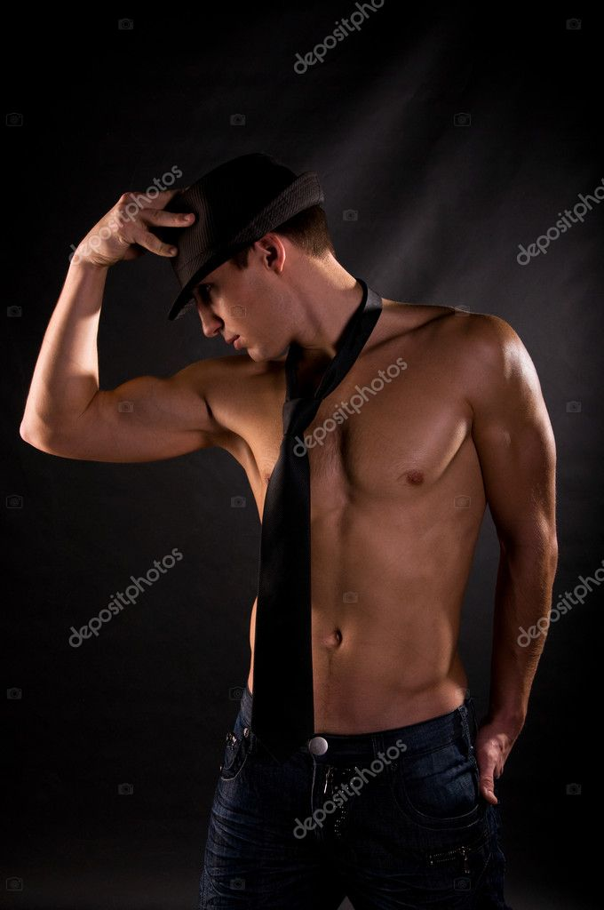 Dramatic light photo of muscular young man in front of black background — Foto Stock #1991699