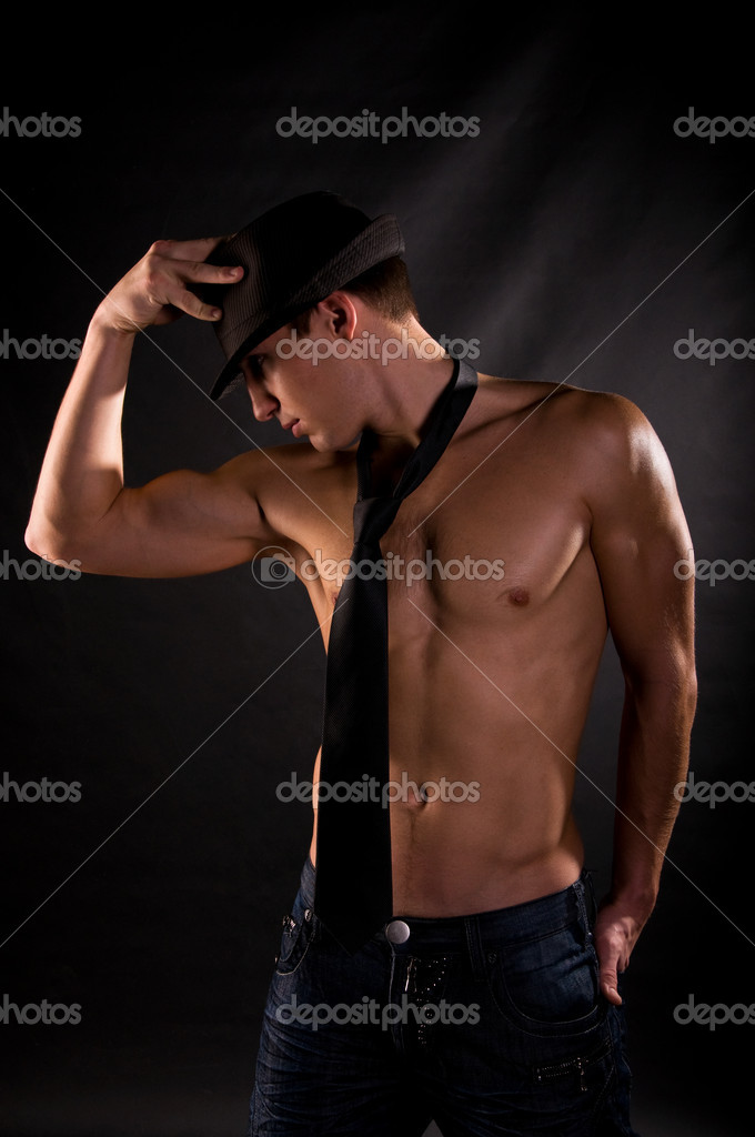 Dramatic light photo of muscular young man in front of black background  Zdjcie stockowe #1991699
