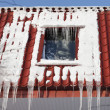 Icicles on building roof at winter day - Stock Photo