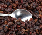 Raisin background and teaspoon — Stock Photo