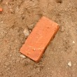 One brick on sand — Stock Photo