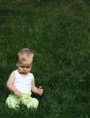 Liitle menino em uma grama — Fotografia Stock