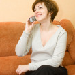 Smiling young woman talking by phone — Stock Photo