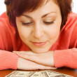 Doubting young woman with money — Stock Photo