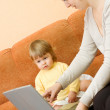 Mother with daughter on sofa with laptop — Stock Photo