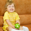 Smiling girl in yellow with green apple — Stock Photo