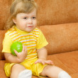 Little girl in yellow eat green apple — Stock Photo