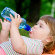 Little girl drinks water from a bottle — Foto Stock