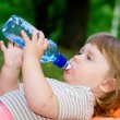 Little girl drinks water from a bottle — Stock Photo