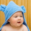 Royalty-Free Stock Photo: Small smiling baby in blue towel on bed
