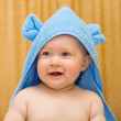 Small smiling baby in blue towel — Stock Photo