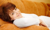 Relaxing smiling young woman in white dr — Stock Photo