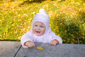 Smiling baby with yellow leaf — Stock Photo