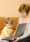 Small girl and mother with laptop — Stockfoto