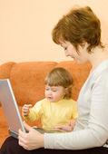 Small girl and mother with laptop at hom — Stock Photo