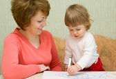 Small drawing girl with mother at home — Stock Photo