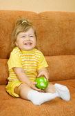 Niña sonriente en amarillo con verde manzana — Foto de Stock