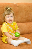 Little girl in yellow eat green apple — Stock Photo