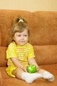 Little smiling girl in yellow eat apple — Stock Photo