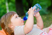 Girl drinks water from a bottle — Stock Photo