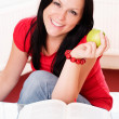 Smiling brunette woman holding an apple — Stock Photo