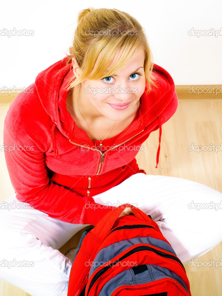 Smiling blond teenager sitting on floor with backpack  Stock Photo #1855360