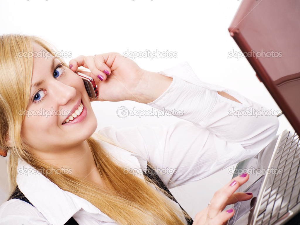 Smiling blond woman working with computer and talking by phone in office — Stock Photo #1855534
